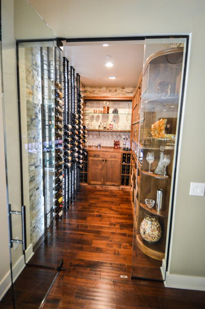 This design uses traditional wood, modern metal, and glass to transform this office space into a beautiful, transitional wine room.